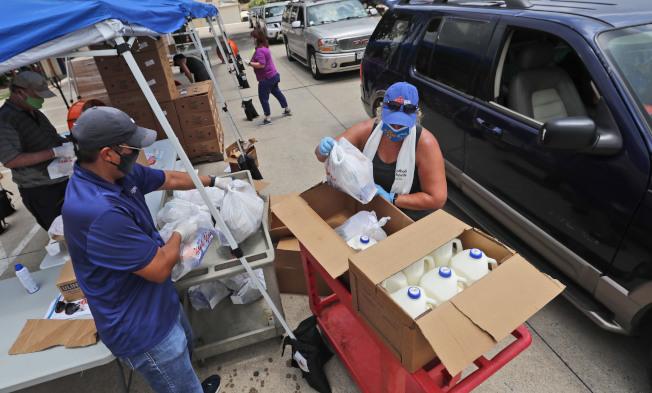佛州與德州都報出單日確診病例新增案件持續增加。圖為德州達拉斯戴著口罩的居民正分配食。(美聯社)