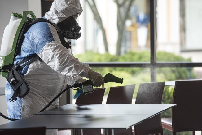佛州與德州都報出單日確診病例新增案件持續增加。圖為德州的餐館員工正在清理座位。(美聯社)