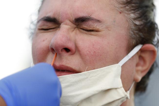 棉籤伸入鼻腔採樣時,有點不舒服。(美聯社)