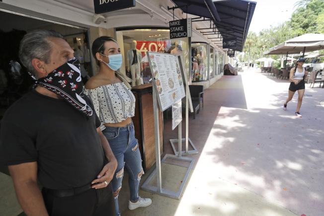 佛州過去兩周總新冠確診人數從10萬翻倍至5日的20萬例。圖為佛州兩名餐館工作人員站在門口等待顧客。(美聯社)