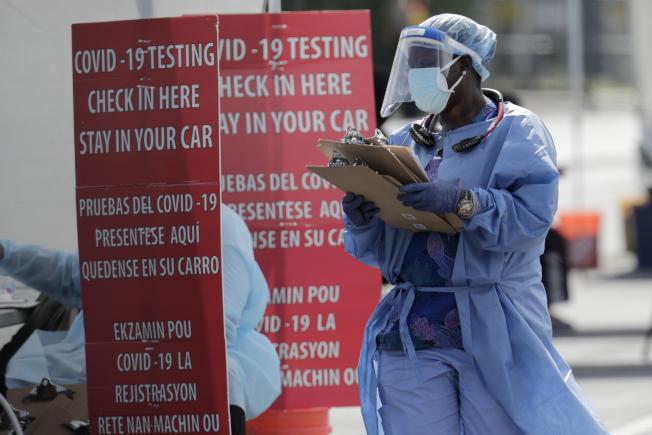 佛州過去兩周總新冠確診人數從10萬翻倍至5日的20萬例。圖為佛州一名醫衛人員在檢測病毒現場忙碌工作。(美聯社)
