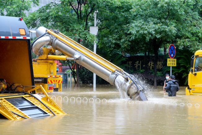 7月6日上午,武漢市洪山區,水務部門排澇車正在進行抽水作業。(中新社)