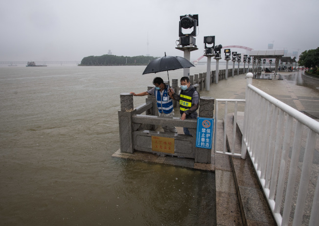7月6日,工作人員在武漢龍王廟觀察水情。(新華社)