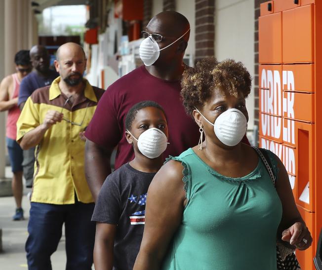 全美各大賣場希望州長能下令強制在公共場合戴上口罩,降低新冠病毒傳播。圖為在家得寶戴口罩顧客排隊進場購物。(美聯社)