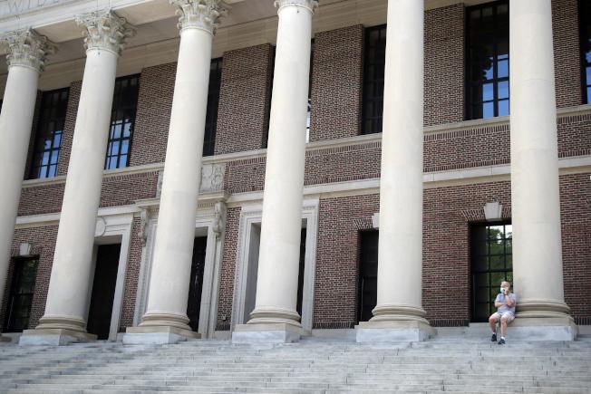 哈佛校園Widener圖書館前,一男子戴著口罩講電話。(美聯社)