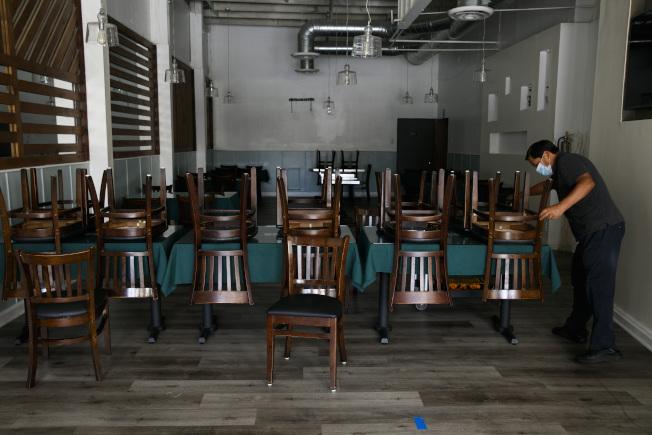 加州洛杉磯,一家秘魯飯店老闆在店內整理桌椅。(美聯社)