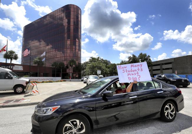川普總統堅持要求秋天復學,並威脅稱,若學校屆時不重開,可能切斷金援。圖為佛州奧蘭多一教師舉著「多少學生得送死?」的標語,抗議貿然重啟學校。(美聯社)