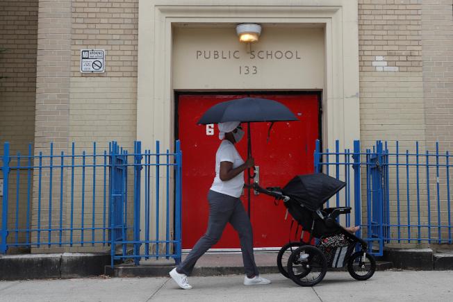 紐約市政府已經制訂9月公校復課的計畫,但最終決定權在紐約州府;圖為一位母親推著嬰兒車,走過曼哈頓公立133小學的門前。(路透)