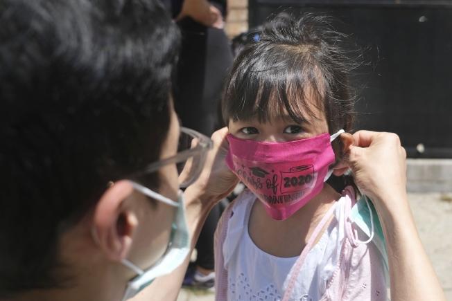 新冠肺炎疫情衝擊,導致許多學校和幼稚園無法開學,家長為了照顧小孩只能先放下工作。圖為新澤西州澤西市一華裔家長為上學前班的女兒戴口戴。(美聯社)