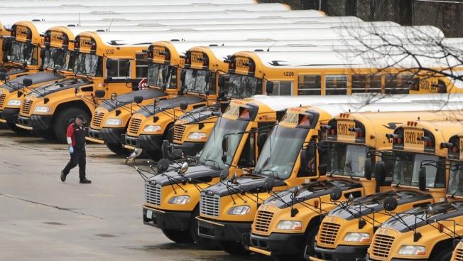 新冠肺炎疫情衝擊,導致許多學校和幼稚園無法開學,家長為了照顧小孩只能先放下工作。圖為學校停課後,成排的校車在停車場閒置。(美聯社)
