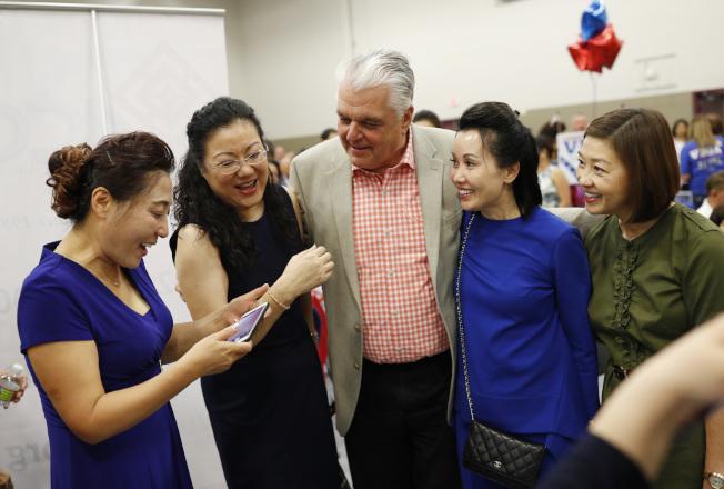 愈來愈多的亞裔選民向民主黨靠攏。圖為2018年內華達州州長候選人Steve Sisolak與亞裔選民相處甚歡。(美聯社)