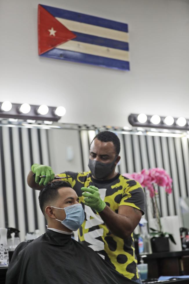 世衛組織終於對外承認新冠病毒在一些情況下,包括室內,可以藉由空氣傳播,而且多在餐廳、合唱團訓練和健身房等場合爆發。圖為佛州復工後,一髮廊為顧客理髮。 (美聯社)