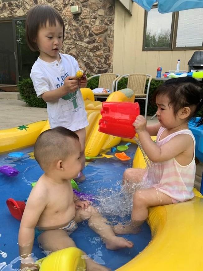 天氣太熱,幾乎家家戶戶都搬出充氣水池讓孩子玩水消暑。(張永斌提供)