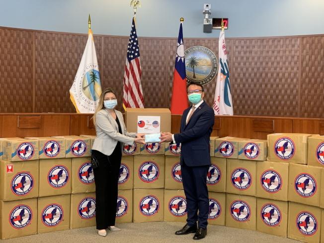 經文處處長錢冠州(右)代表屏東縣政府捐贈防疫物資給陽光小島灘市,該市副市長思薇欽(左)代表接受。(孫博先提供)