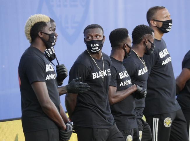 美足大聯盟在佛州比賽,Columbus Crew隊的成員站在場邊,全戴上口罩。佛州疫情近日飆升。(美聯社)