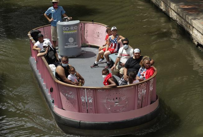 德州聖安東尼奧的遊客們搭船遊河,並非人人都戴口罩。德州多數地區已強制在公共場合必須戴口罩。(美聯社)