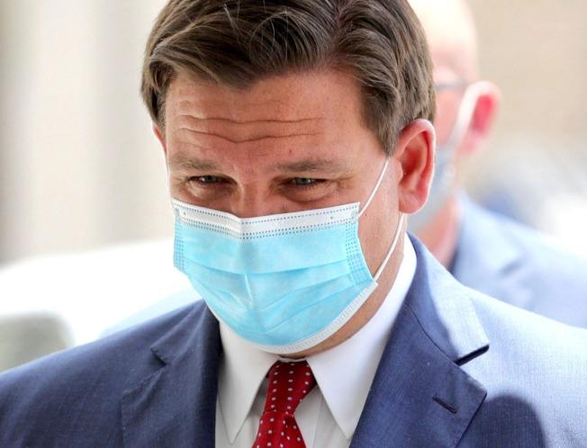 佛州州長德桑提斯(Ron DeSantis)10日在奧蘭多說明佛州疫情時,戴著口罩。3月初大紐約地區疫情嚴重時,佛州州長先開第一槍,要求去過紐約的民眾要自我隔離。(美聯社)