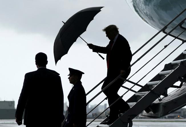 川普總統10日赴佛州,他抵達羅德岱堡時,自己撐著傘下機。(路透)