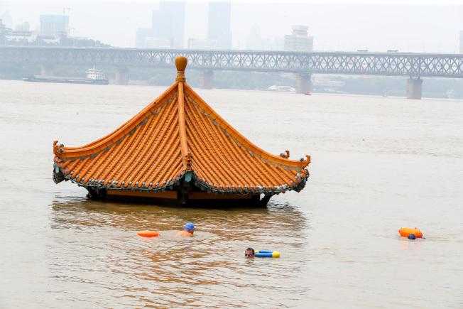 湖北武漢黃花嘰親水平台一座涼亭已遭大水淹沒,但10日仍有民眾「游興」不減,在附近游泳。(中新社)