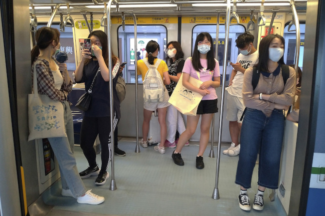 台北捷運一車廂內,可見乘客們都佩戴了口罩。(美聯社)