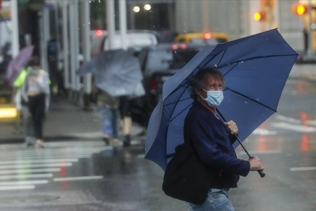 10日,一名紐約客撐傘前行。(美聯社)