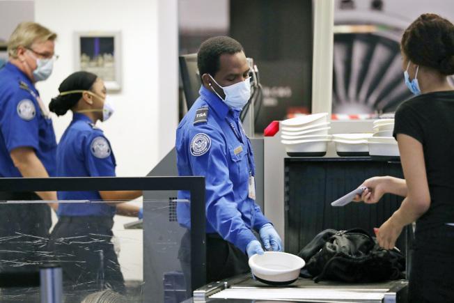 負責機場安檢的運輸安全局人員暴露在新冠肺炎抗疫前線,已有超過1000人染疫。圖為西雅圖安檢員檢查搭機旅客。(美聯社)