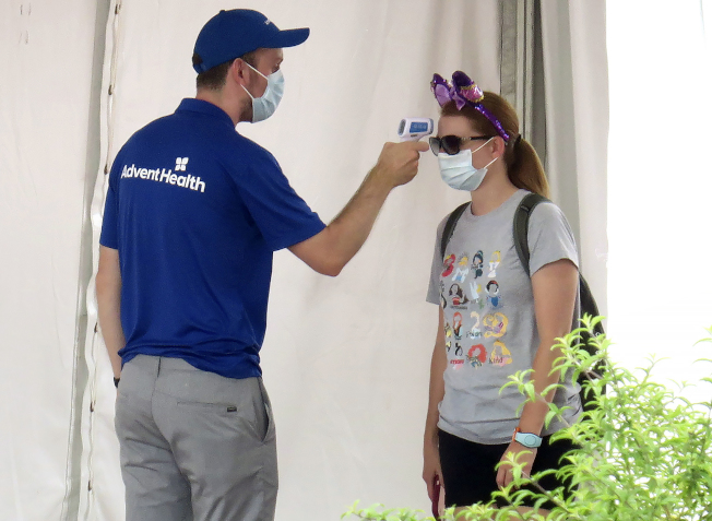佛州奧蘭多的迪士尼世界主題樂園,11日重開,啟動諸多防疫措施。圖為入園遊客須戴口罩並測量體溫。 (美聯社)