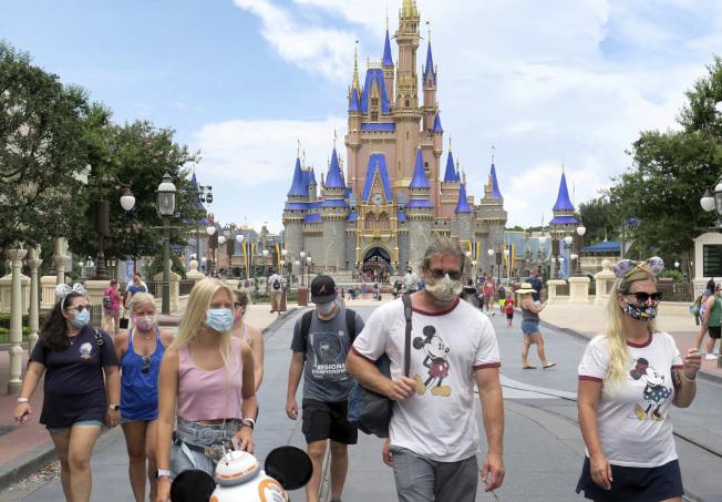 佛州迪士尼11日位於奧蘭多的迪士尼世界主題樂園,園方入園遊客須戴口罩並測量體溫。(美聯社)