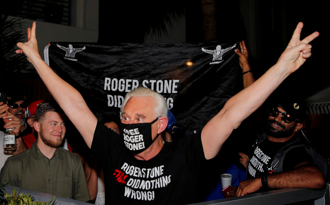獲川普總統減刑後,史東在佛州家門前戴著口罩向支持者歡呼。(路透)