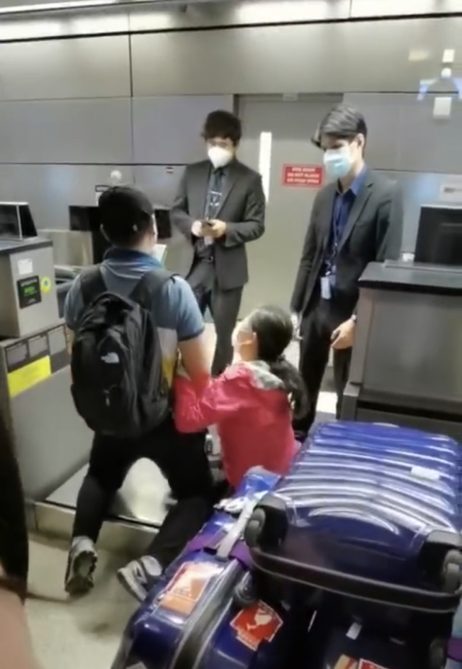 一名中國成年男子和他的母親日前跪在LAX機場某中國航空公司的行李稱重台上。(視頻截圖)