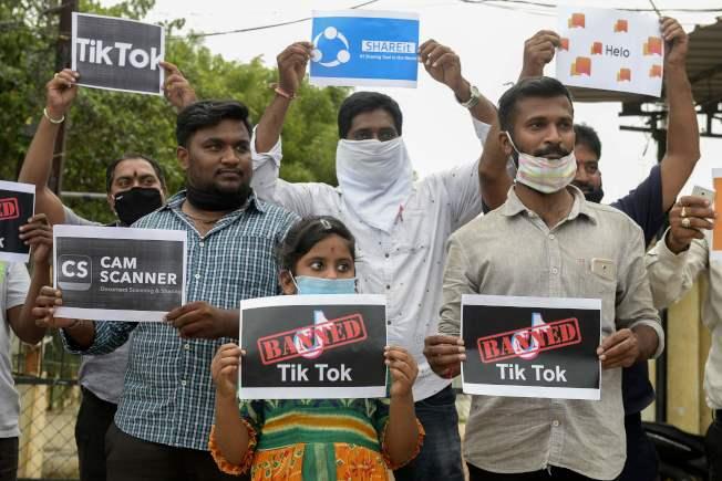 印度以國安及隱私疑慮為由,禁止使用59種中國手機應用程式。圖為印度民眾拿海報支持政府禁止TikTok等中國手機應用程式軟體。(Getty Images)