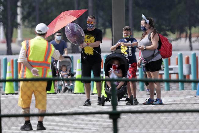 圖為一家大小入園遊客,戴著口罩,聽從園內人員解說。(Getty Images)