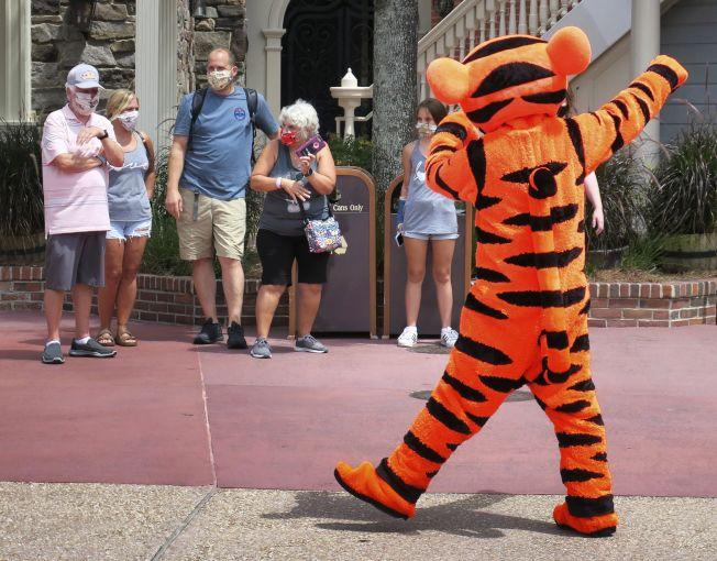 佛州 奧蘭多的迪士尼世界主題樂園,11日重開。入園遊客戴口罩觀賞景點。(美聯社)