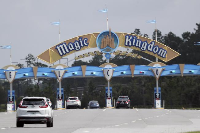 佛州 奧蘭多的迪士尼世界主題樂園,11日重開,啟動諸多防疫措施。圖為入園遊客正駕車進入遊樂區。(美聯社)
