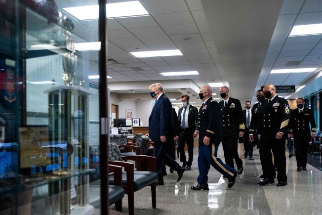 川普總統11日探視馬里蘭華特里德軍醫院,在院內軍官陪同下親察,首次公開戴上口罩露面。(Getty Images)