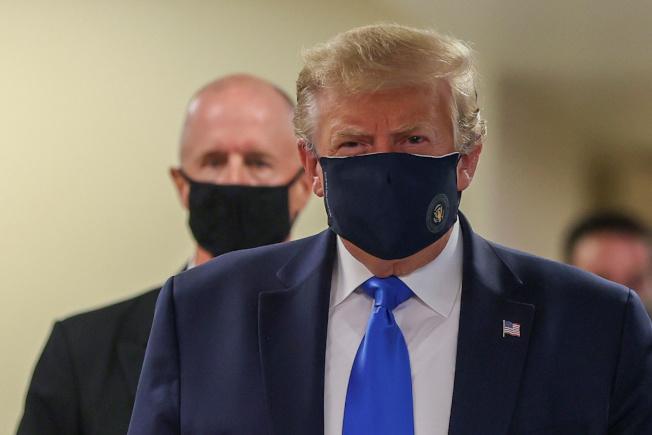 川普總統11日探視馬里蘭華特里德軍醫院,首次公開戴上口罩露面。(路透)