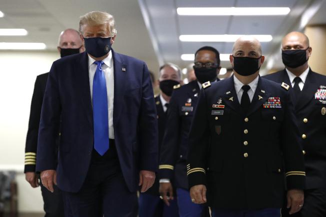 在疫情期間一直抗拒戴口罩的川普總統,11日訪問華特里德軍醫院時,難得地戴上口罩;這是他自新冠疫情暴發以來,首度戴著口罩公開亮相。(美聯社)