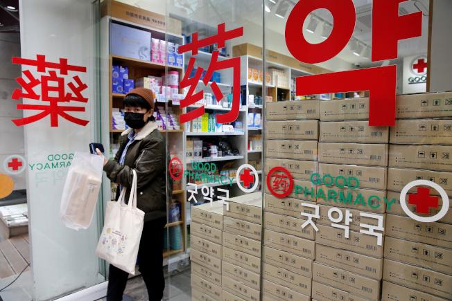 南韓政府十二日宣布,即日起民眾可在藥局、超市和超商等地無限量購買口罩。圖為一名遊客一月卅一日在南韓首爾明洞藥局購買口罩。(路透)