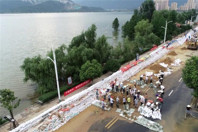 江西省鄱陽湖沿岸居民11日沿堤防堆放大量沙包,鄱陽湖口水位至12日下午4時直逼22.5公尺最高防洪水位。(中新社提供)