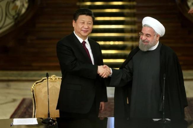 圖為中國國家主席習近平(左)2016年1月23日訪問伊朗期間,在德黑蘭總統官邸薩德阿巴德宮,與伊朗總統羅哈尼握手。(美聯社)