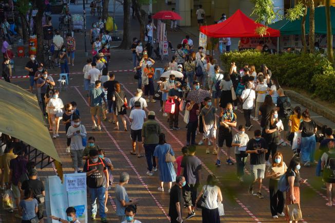 為期2天的香港民主派立法會議員初選投票12日晚間9時結束,總計參與民主派初選投票的港人將近60萬人。圖為香港街頭排隊參與初選投票民眾。(美聯社)