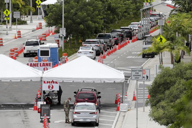 佛州單日確診人數創下全美新高紀錄。圖為佛州邁阿密市居民12日駕車「得來速」檢測新冠病毒。(美聯社)