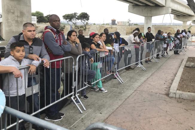 在美墨邊界排隊等候進入美國申請庇護的移民。(美聯社)