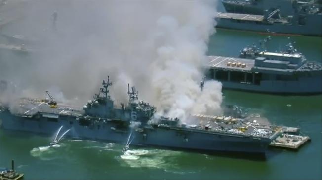 靠泊加州聖地牙哥海軍基地的美軍兩棲攻擊艦「好人理查號」12日上午驚傳爆炸起火,不斷冒出滾滾濃煙。圖為消防隊正在撲滅艦上火勢。(美聯社)