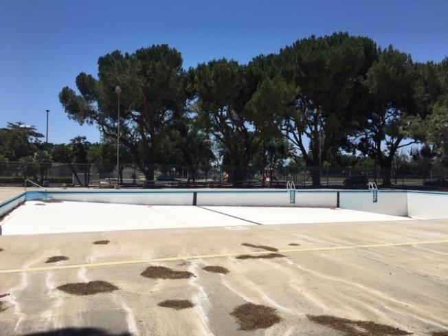 受疫情影響,許多地區的公共游泳池關閉,與往年盛夏季節熱鬧消暑景象完全不同。(記者楊青/攝影)
