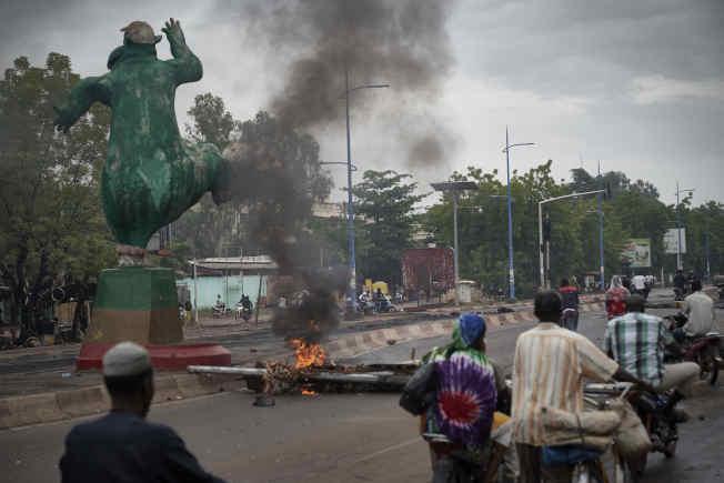 馬利示威者11日在首都巴馬科的烈士橋上架設路障,部分障礙物起火。(Getty Images)
