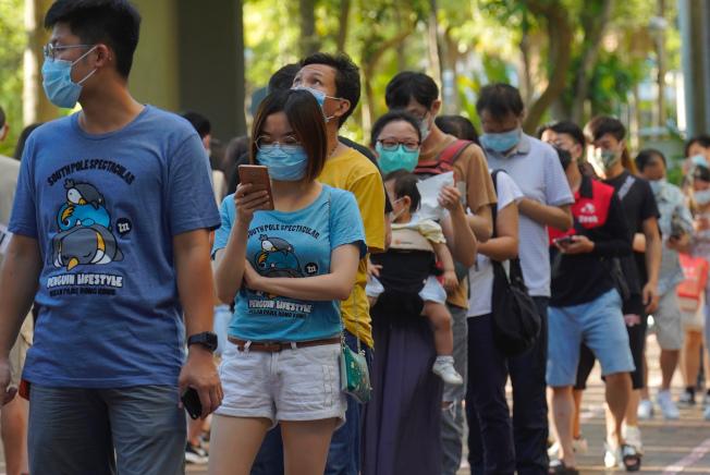 香港民主派立法會議員初選12日投票, 電子投票者加上現場投票,總計參與民主派初選投票的港人超過60萬,出乎意料。圖為年輕一代攜家帶眷,排長隊投票。(美聯社)