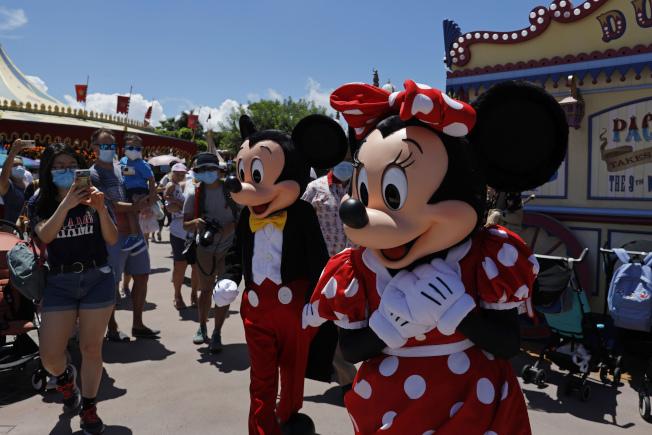 香港新冠肺炎新增確診病例增加,將自15日起暫時再關閉香港迪士尼樂園。圖為6月18日開放時,米奇和米妮迎接遊客。美聯社