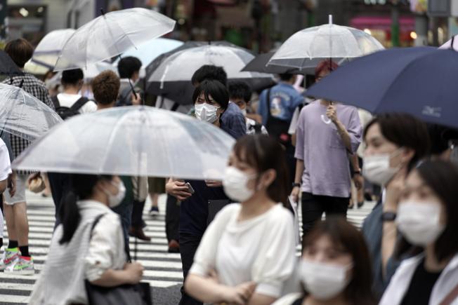 日本東京新宿區一座劇場的偶像舞台表演發生新冠肺炎群聚感染,已知男星山本裕典及演員、工作人員等37人確診,密切接觸者850人。圖為在東京澀谷街上,民眾戴著口罩。美聯社