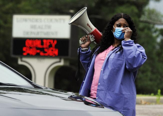 據報導,各州仍有篩檢測試時間等候結果過長,帶源者早已傳染他人。圖為阿拉巴馬州協調員正在告知前來檢測的居民如何進行。(美聯社)